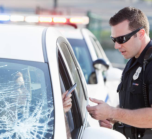 Police officer giving ticket to driver with cracked windshield