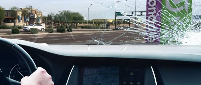 View of Avondale sign from inside a car, looking through a severely-cracked windshield