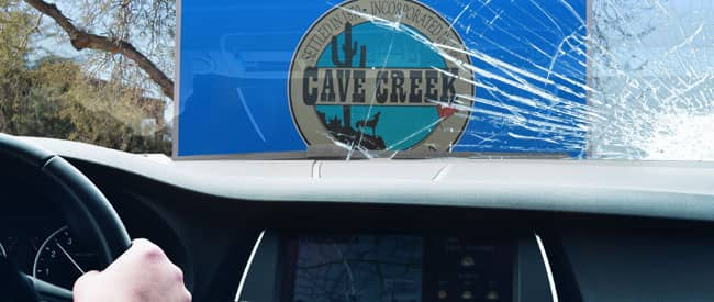 View of Cave Creek sign from inside a car, looking through a severely-cracked windshield