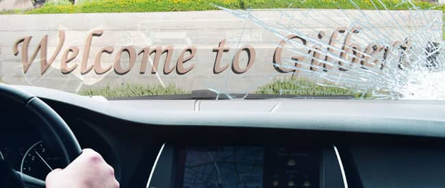 View of Gilbert sign from inside a car, looking through a severely-cracked windshield