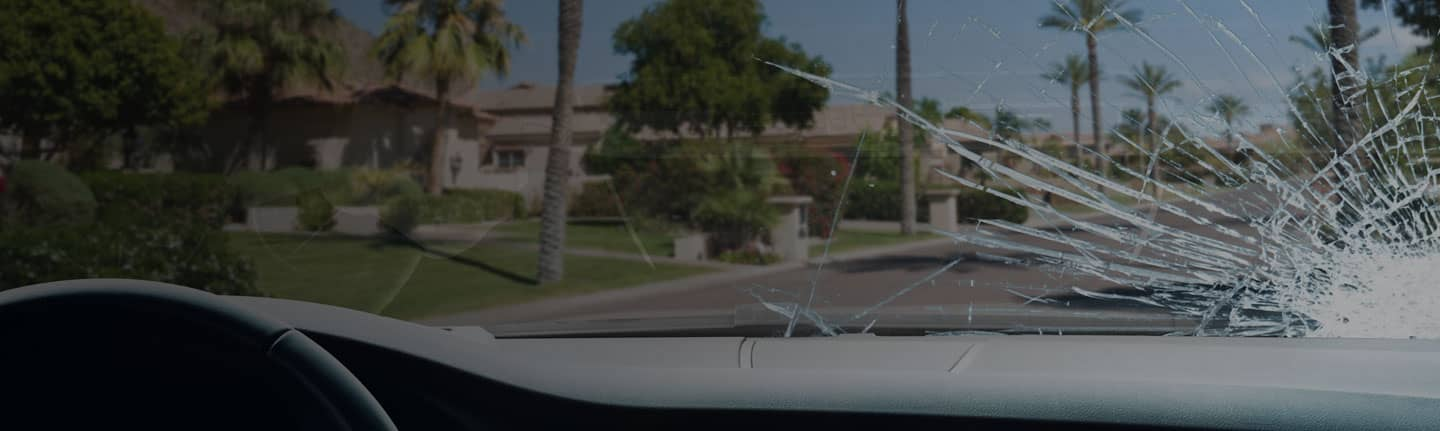 View of Phoenix street and houses from inside a car, looking through a severely-cracked windshield