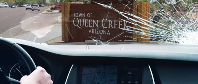 View of Queen Creek sign from inside a car, looking through a severely-cracked windshield