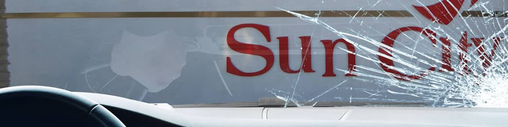 View of Sun City sign from inside a car, looking through a severely-cracked windshield
