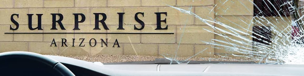 View of Surprise sign from inside a car, looking through a severely-cracked windshield